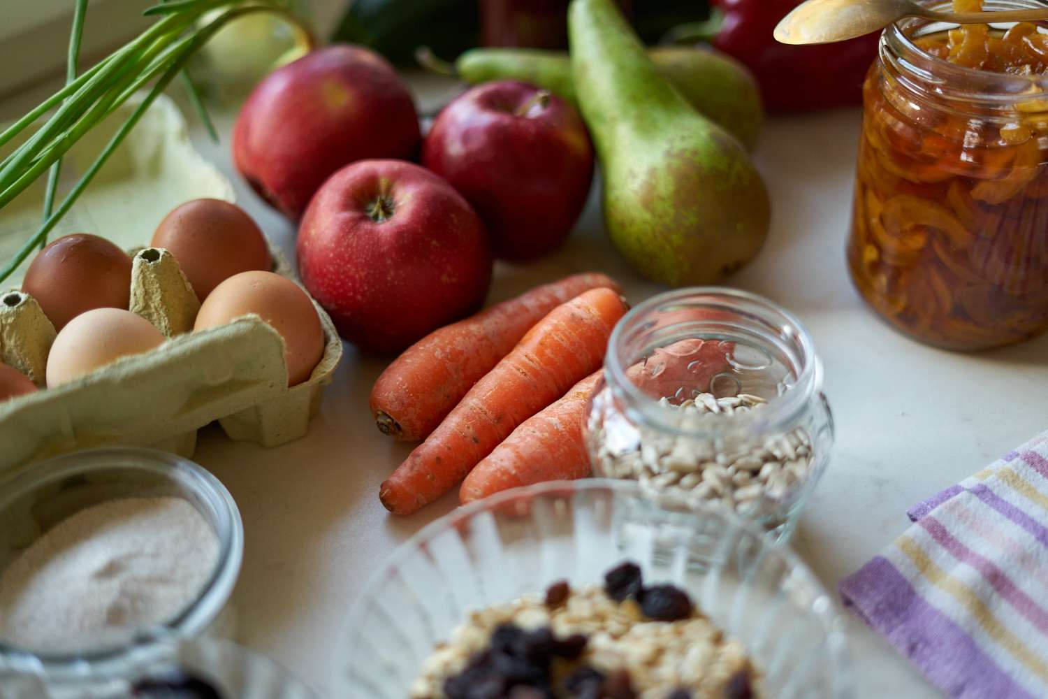 diverse display of healthy foods on counter, including fruits, veggies, eggs, and grains