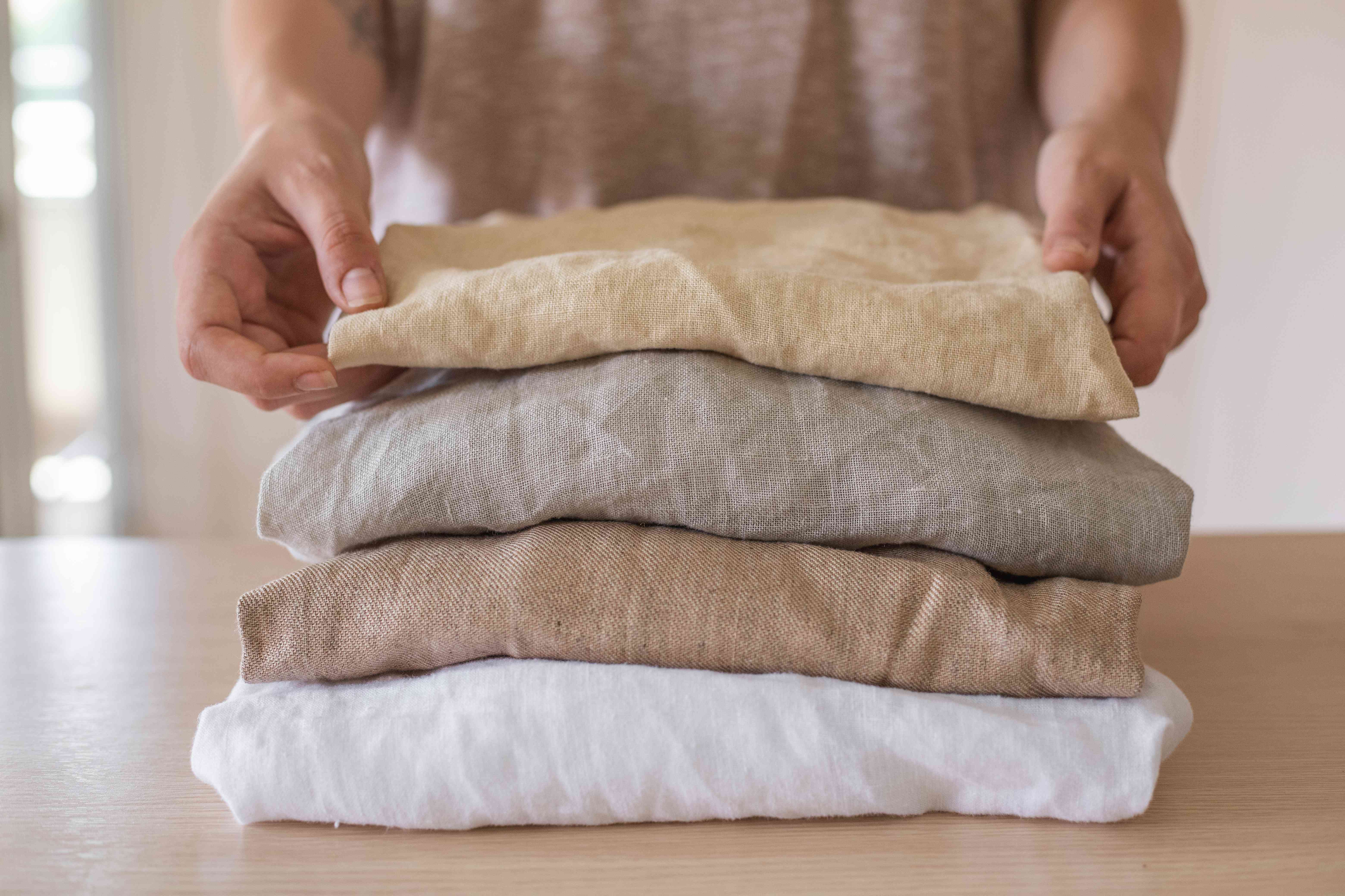 person folds and piles pieces of wrinkled linen clothing in various earth tones