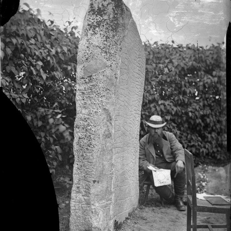 Hans Hildebrand sits beside the Rök Stone