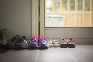 Adult and kid shoes lined up near a door