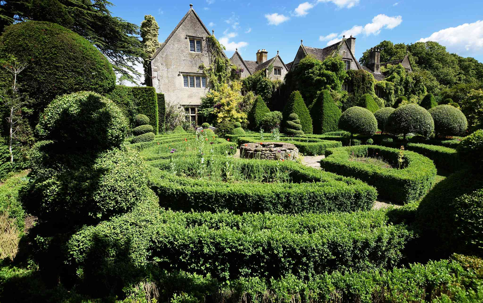 A manicured garden behind a large stone abbey