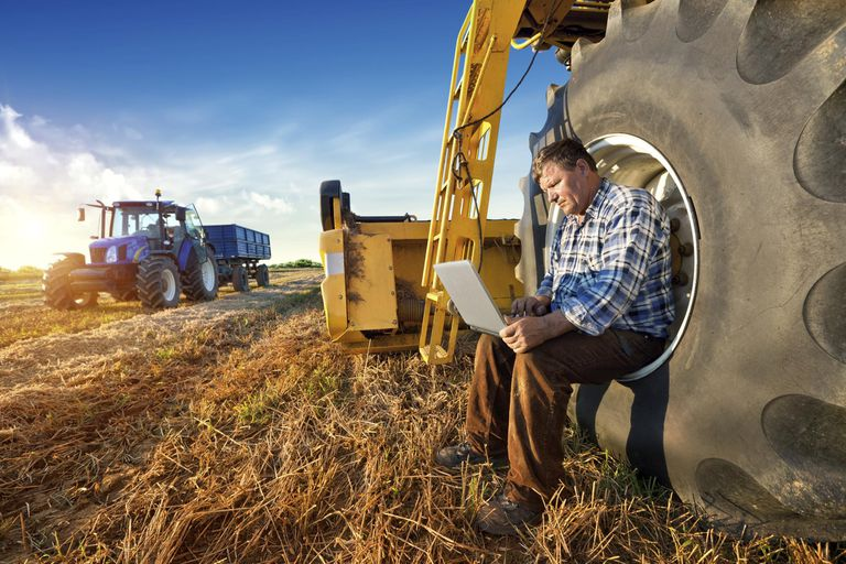 Farmer resting on a tractor wheel while working on a laptop