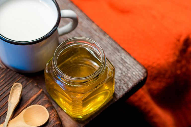 Mug of milk and jar of honey on a wooden table