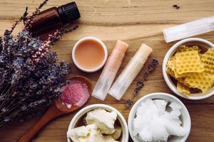 Homemade lip balm surrounded by ingredients and flowers