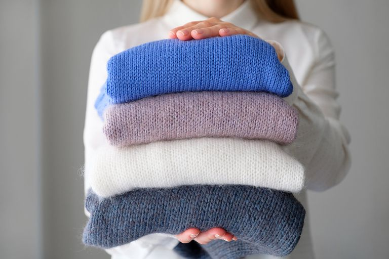A woman holding neatly folded sweaters in blue, white and purple.