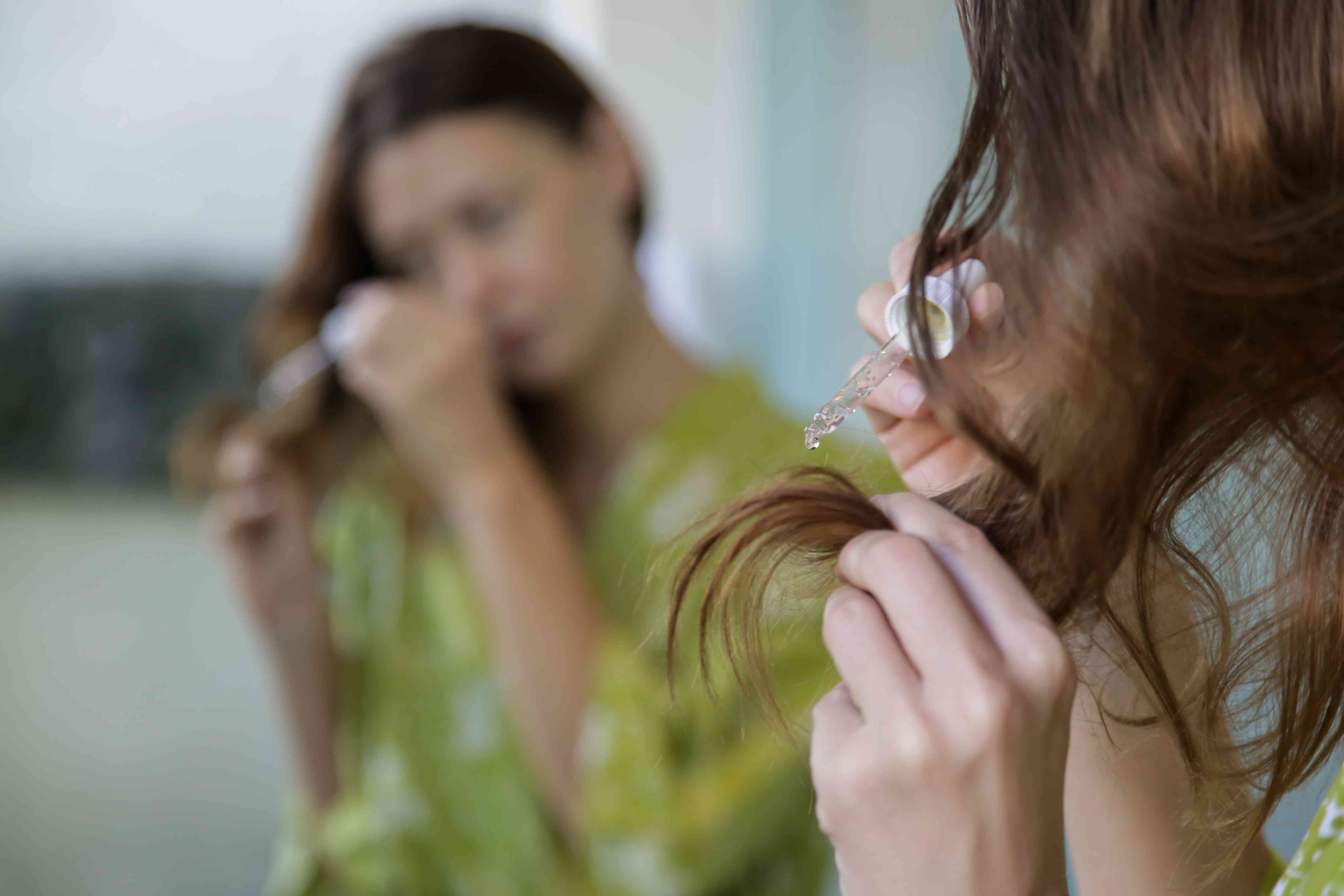 Hair care. Woman applying oil on hair ends in the bathroom in front of the mirror. Split hair tips, dry hair or sun protection concept.