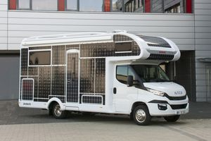 RV parked in a driveway covered with solar panels