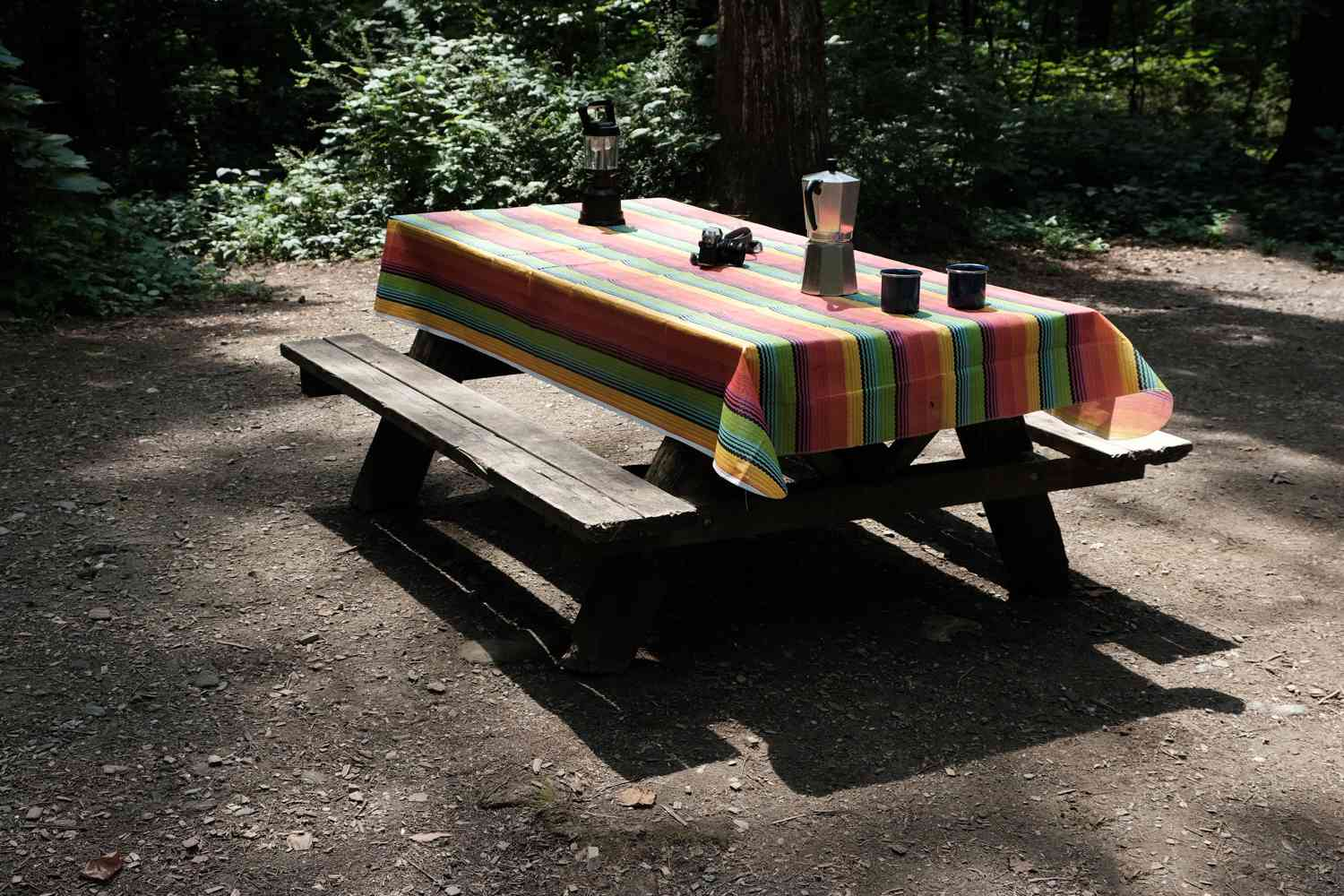 a picnic table in camping ground covered with colorful tablecloth and set for coffee