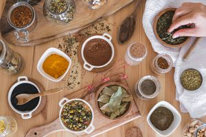 flat lay shots of various spices and dried herbs in jars and ramekins with hand reaching for wooden bowl