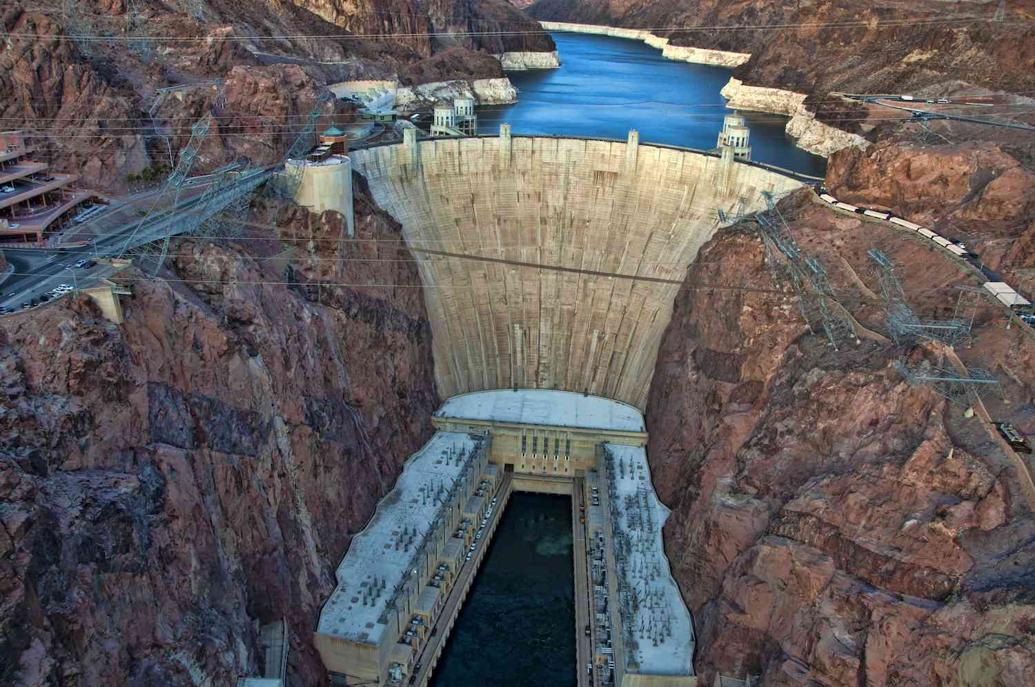 The massive concrete Hoover Dam arched between the reddish rocky landscape