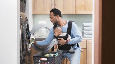 Man doing laundry with kid