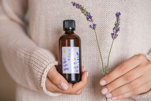 woman in sweater holds DIY lavender oil and a sprig of dried lavender flower