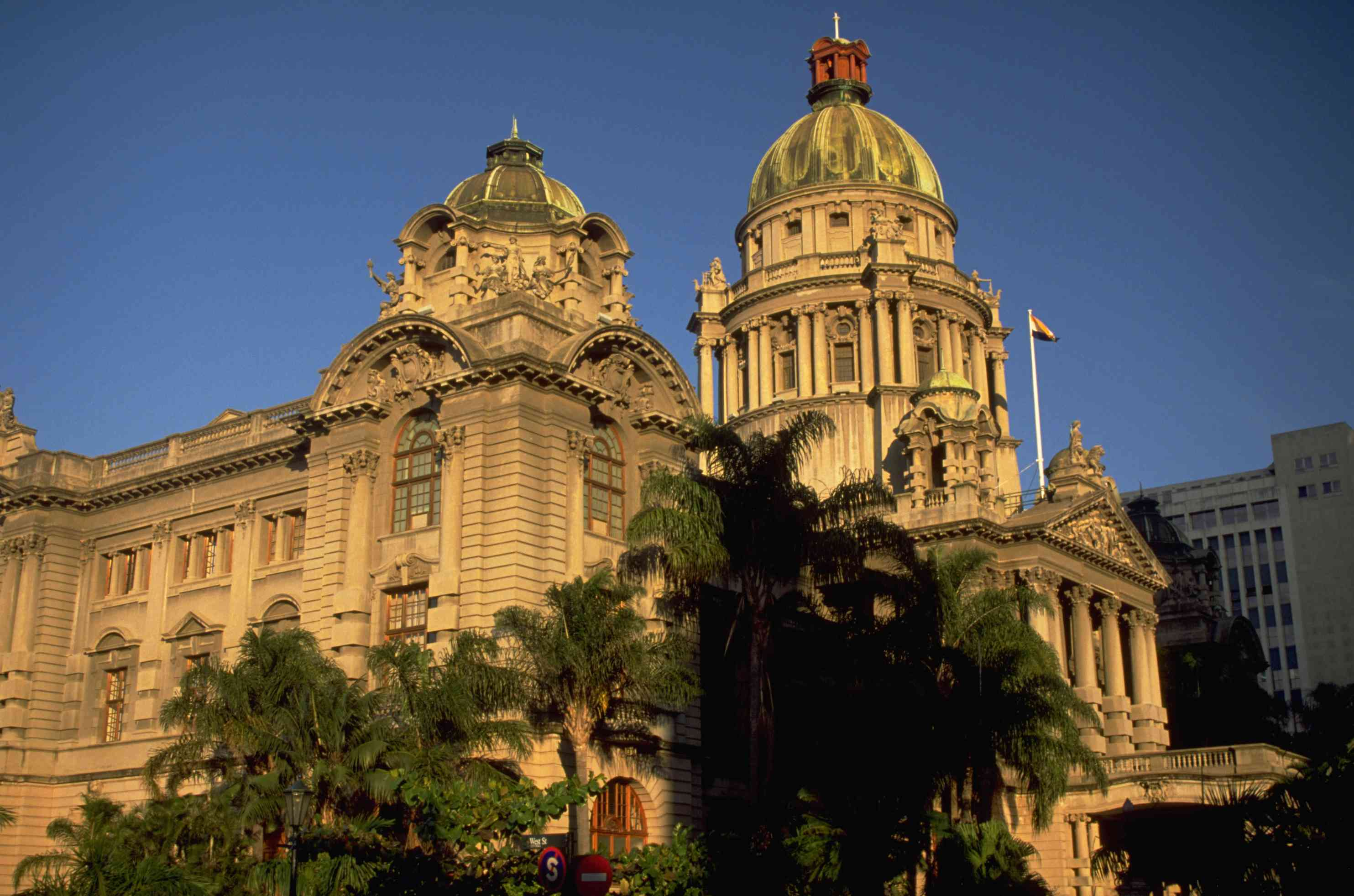city hall in Durban, South Africa with columns and tall dome, lit by setting sun
