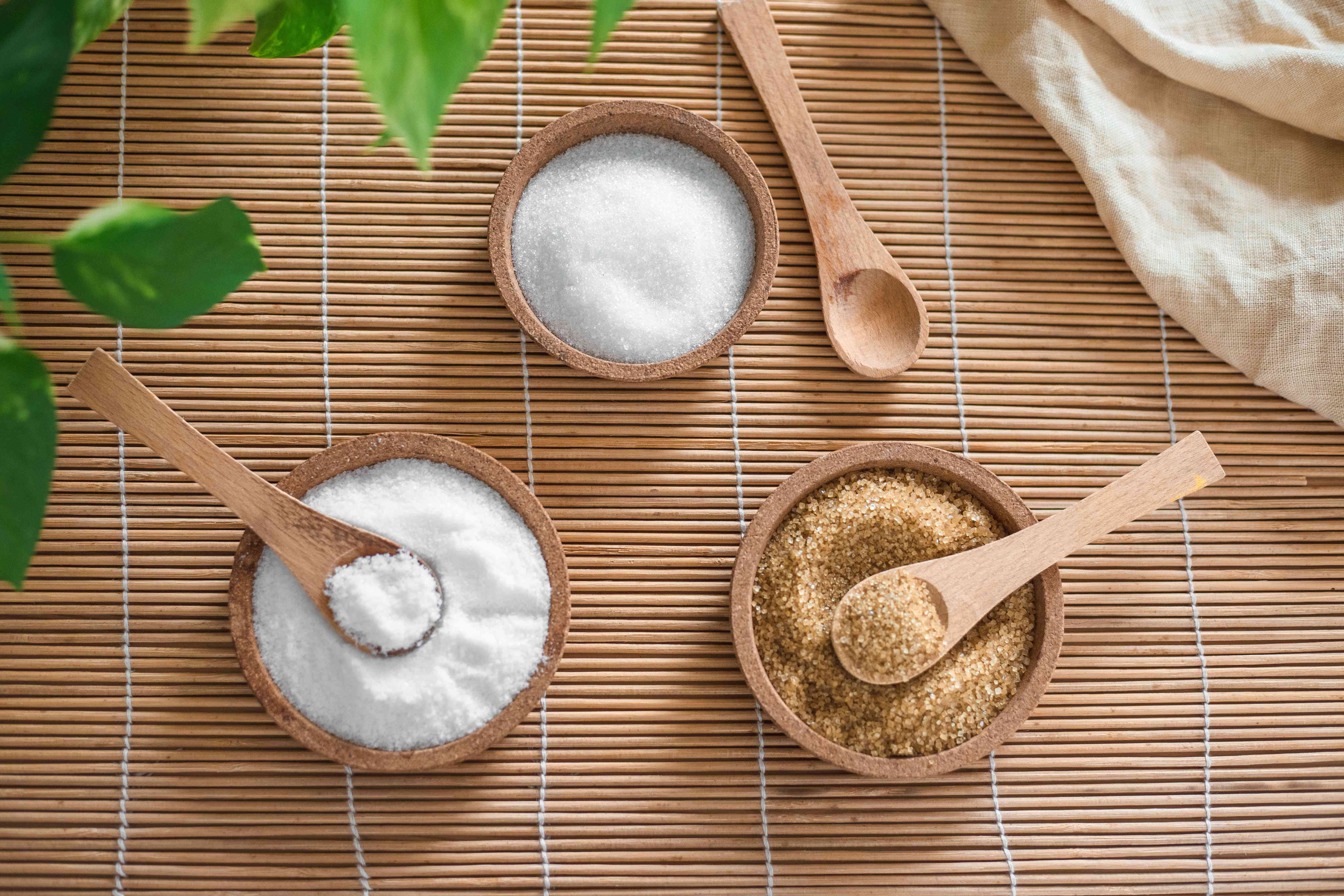 three wooden bowls filled with white sugar, brown sugar, and salt for exfoliation