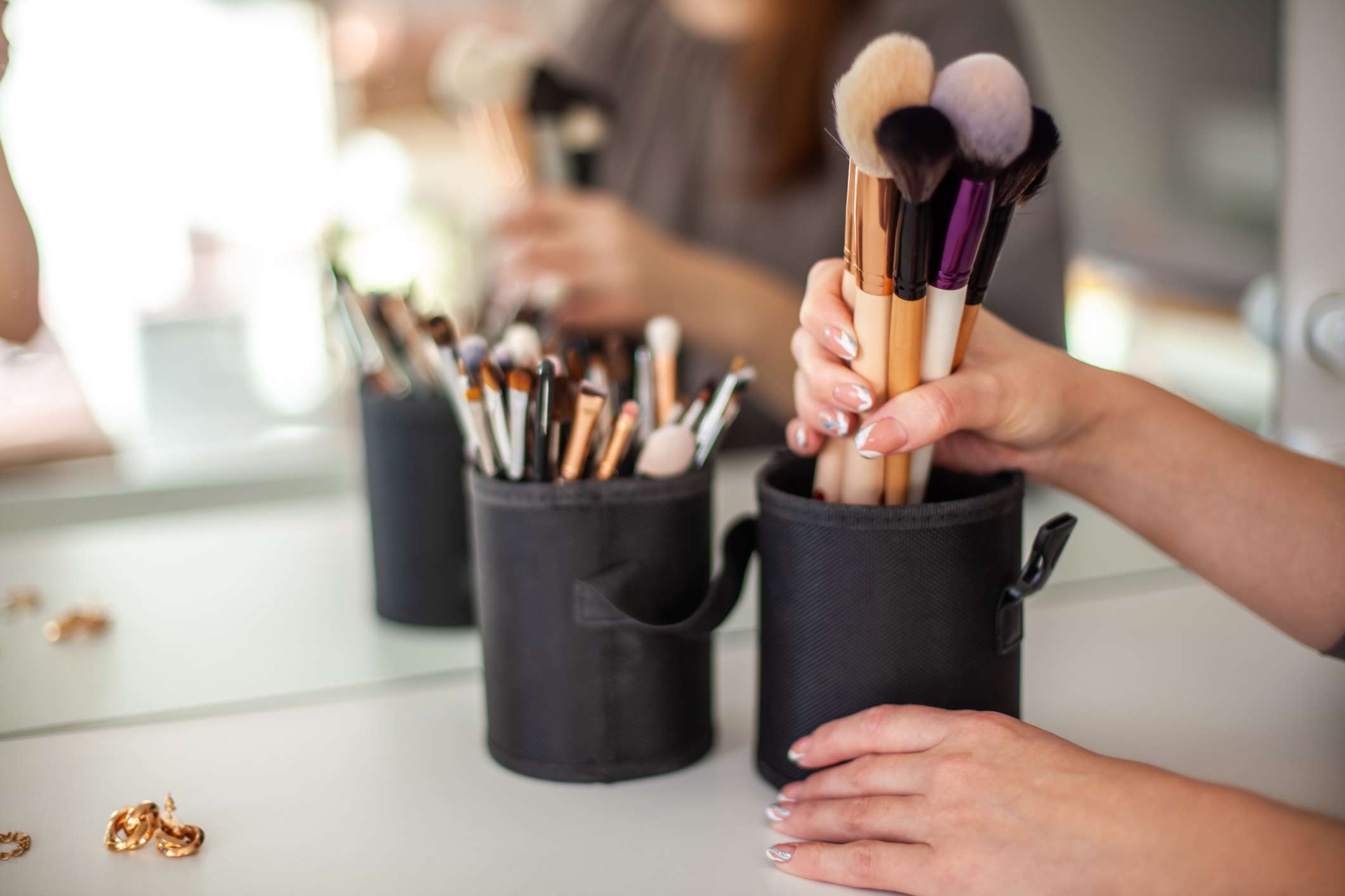 A woman with nail polish picks up brushes from a container.