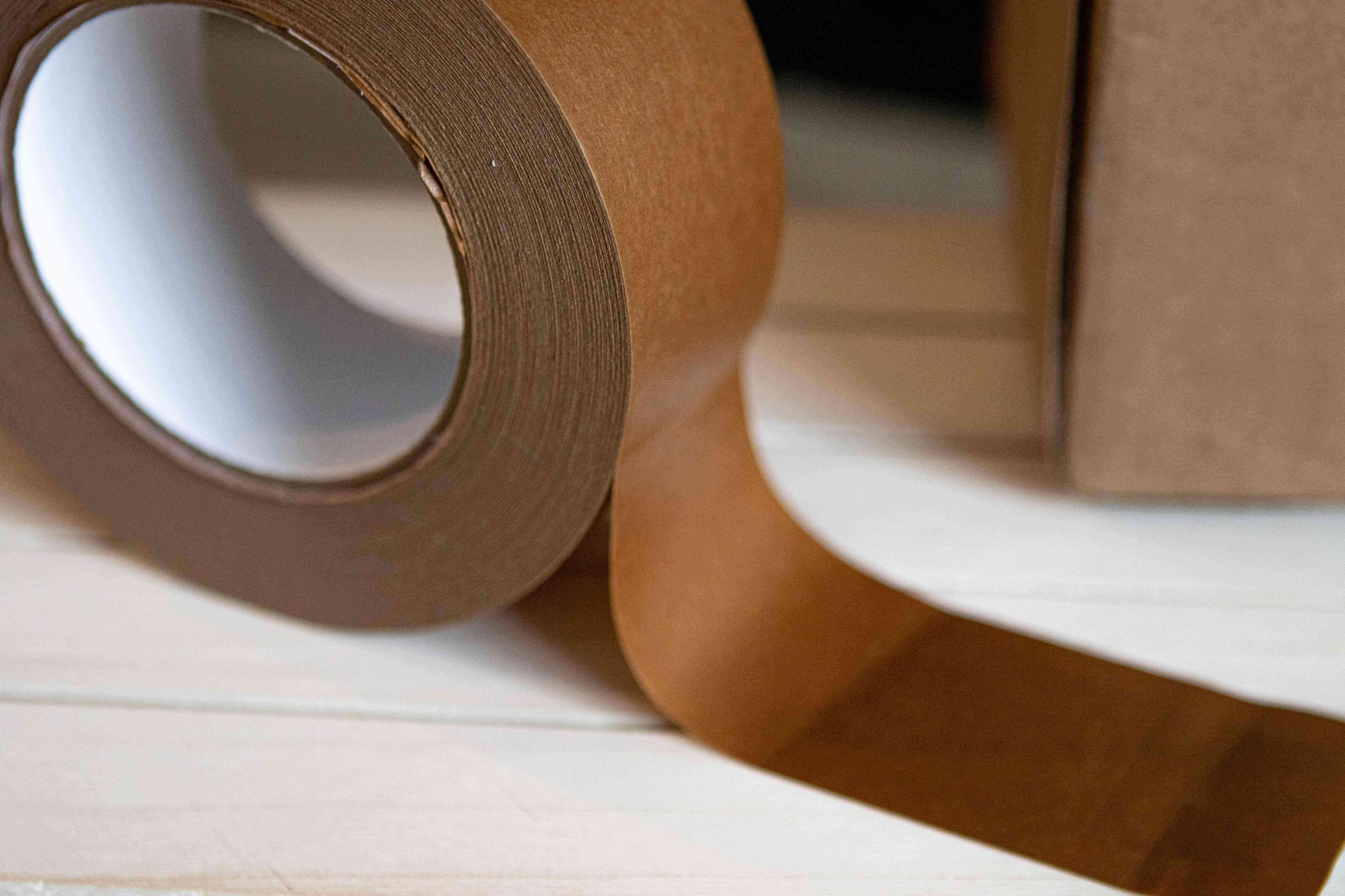 roll of brown recyclable tape with strip stuck to white surface