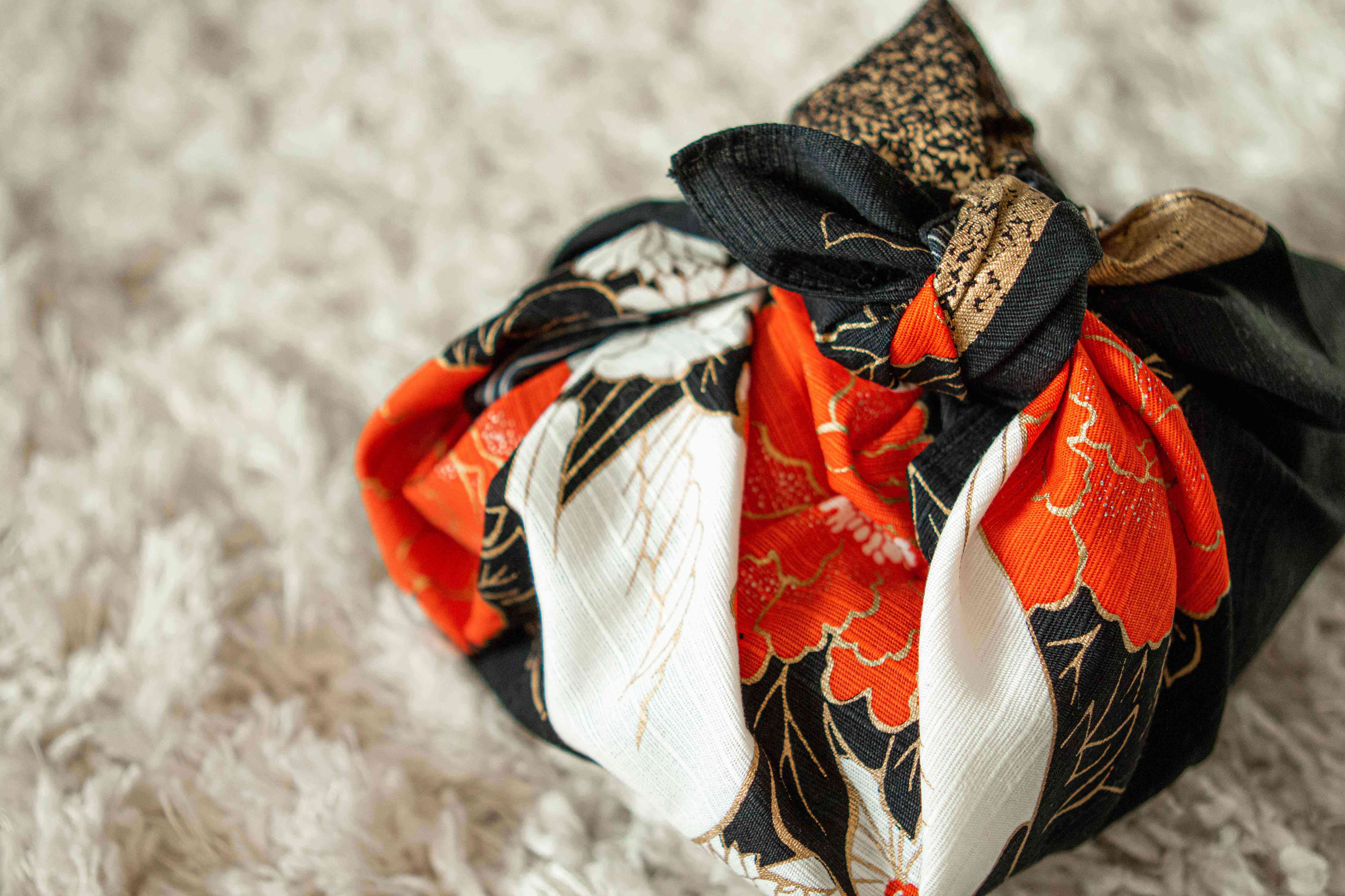 gift box is wrapped with colorful fabric using the Japanese furoshiki method