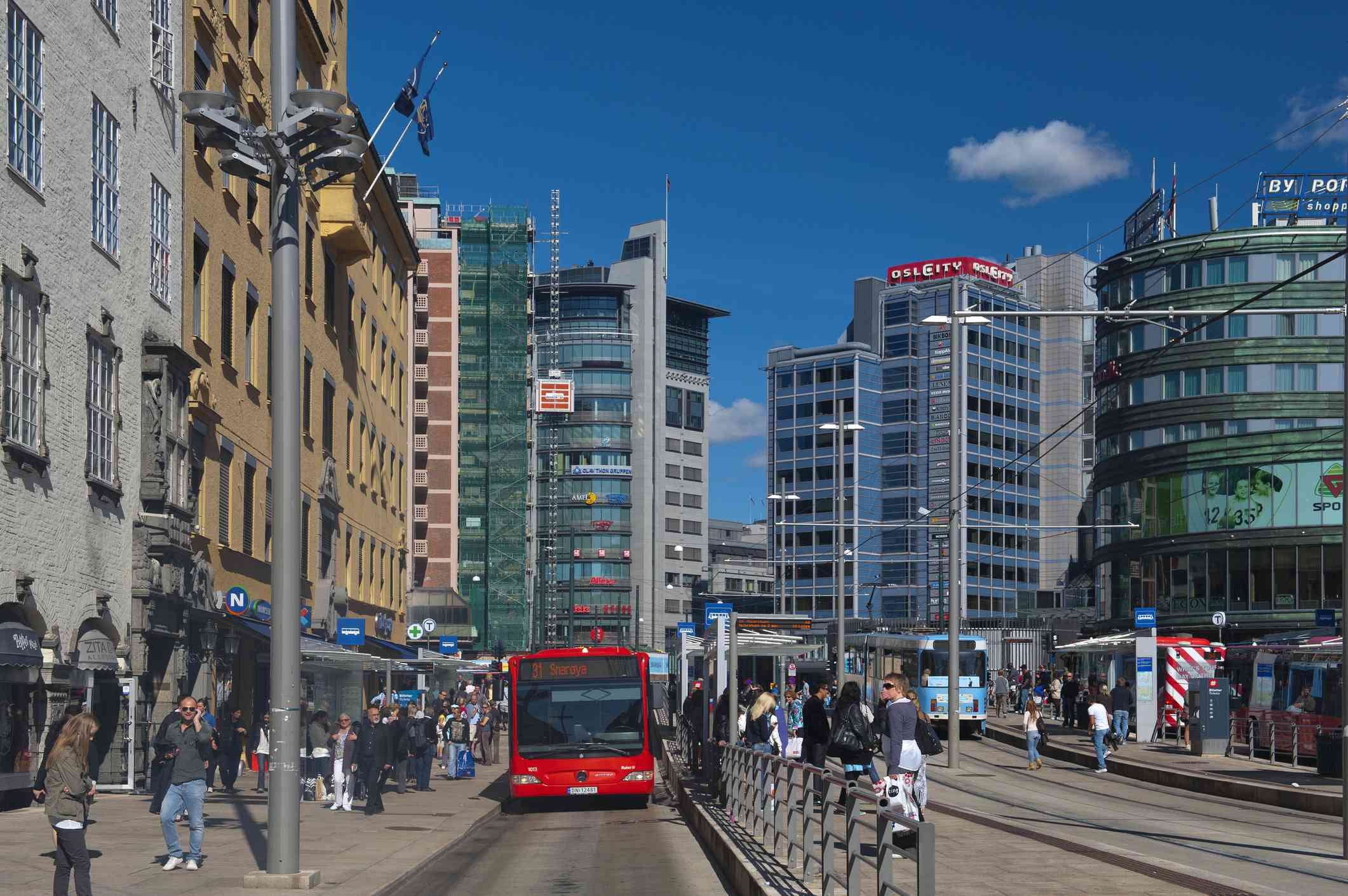 Tall buildings of downtown Oslo, Norway with people walking on clean sidewalks with a red bus in the center of the photo on a sunny day with a bright blue sky with few clouds