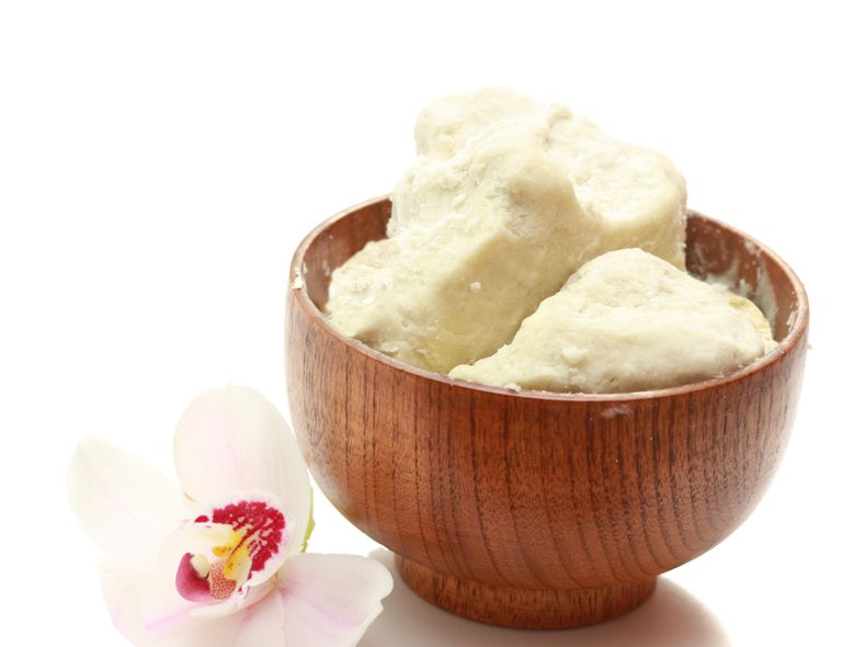 Raw shea butter in wooden bowl with orchid