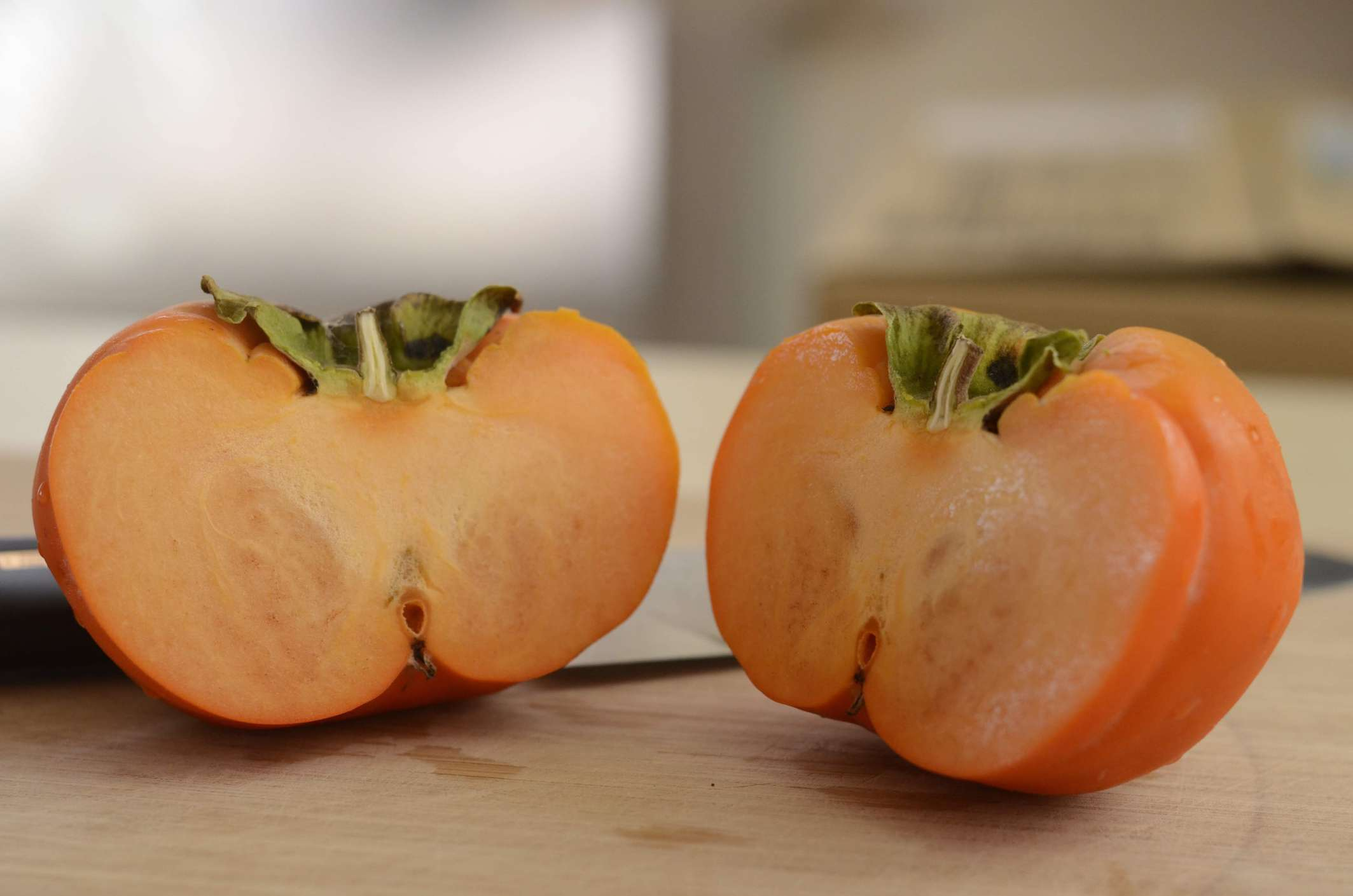 Halved persimmon on a cutting board