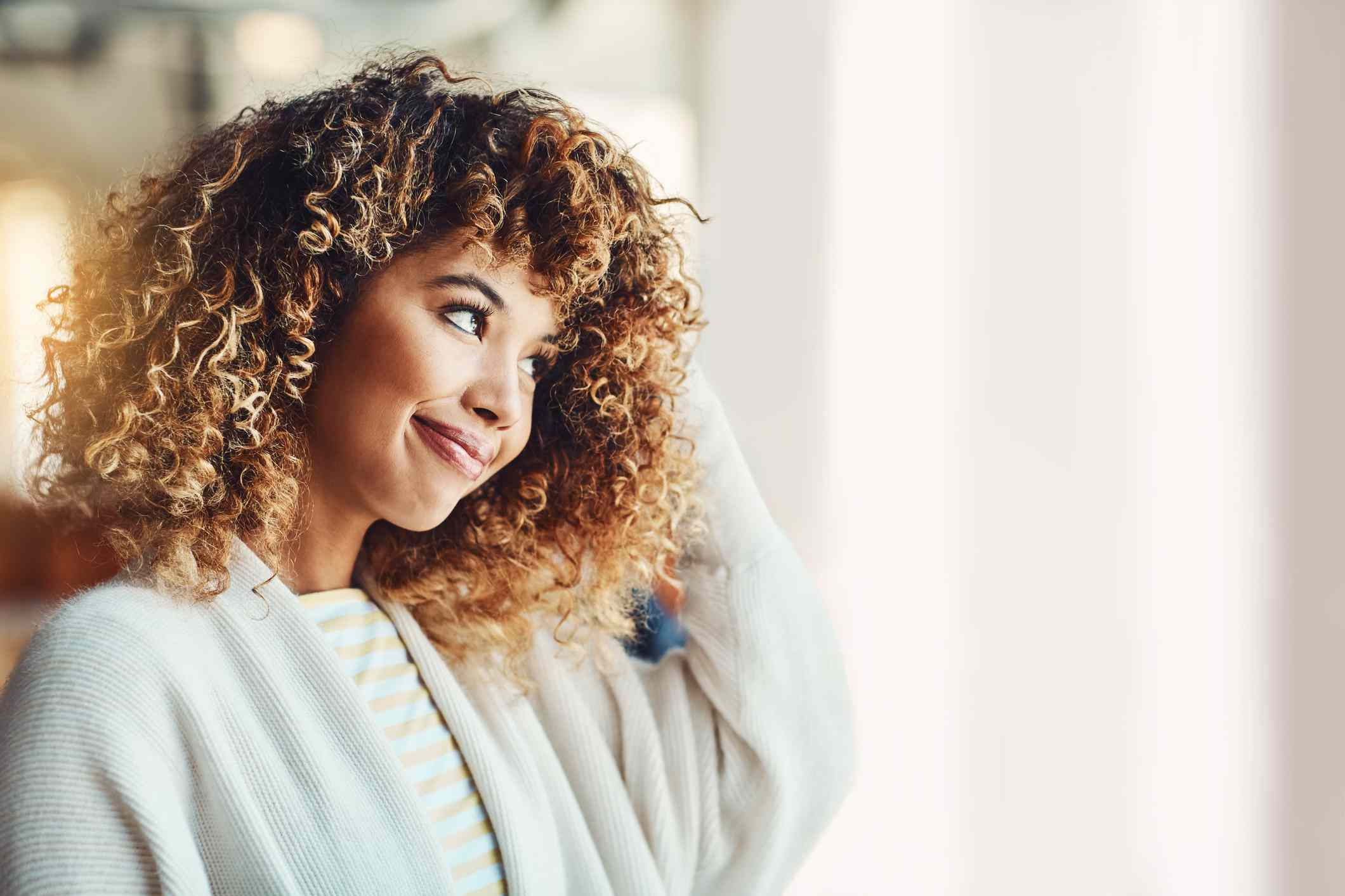 A black woman with curly hair smiles and touches her head.