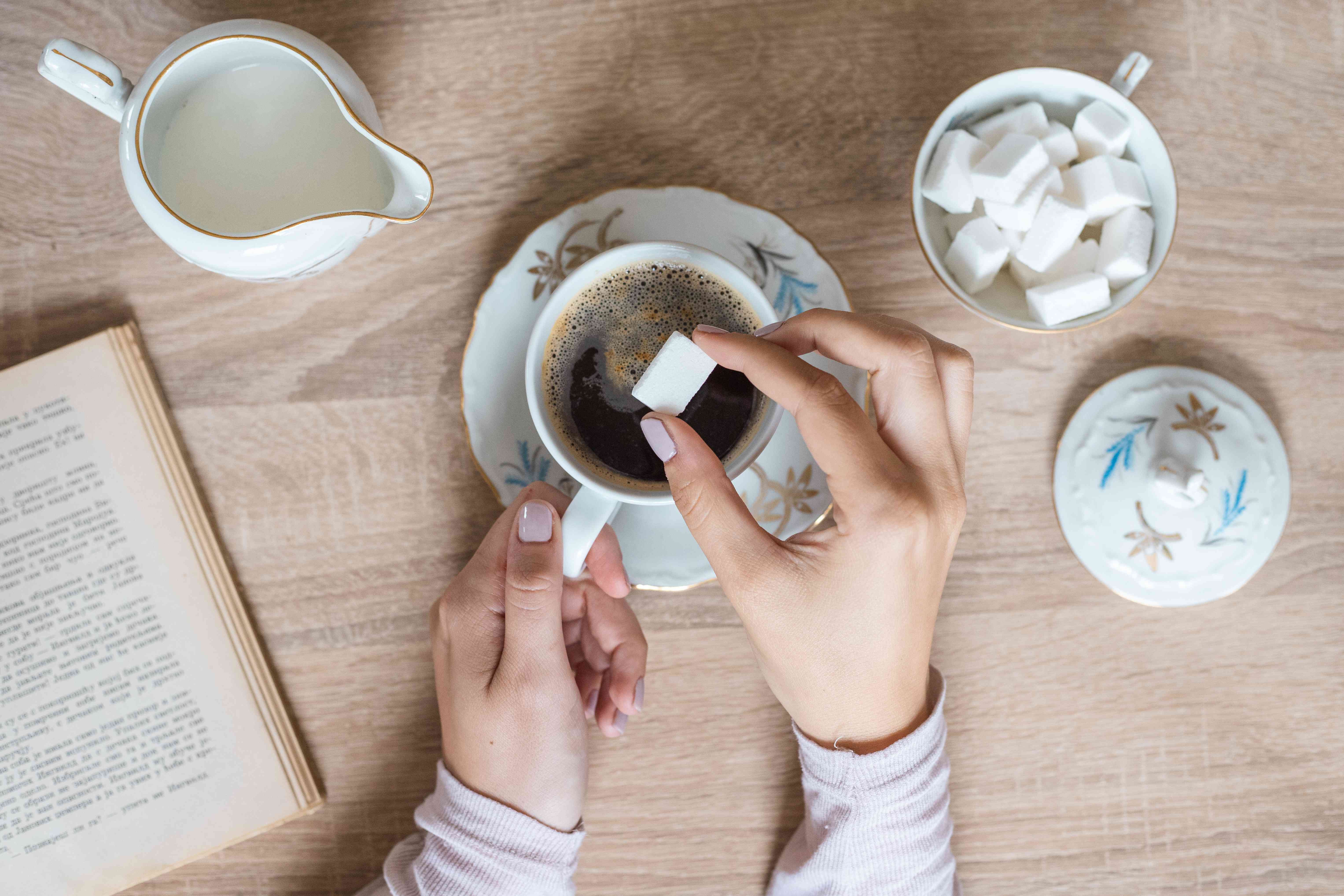 hands place white sugar cube into delicate teacup with cream pitcher on the side