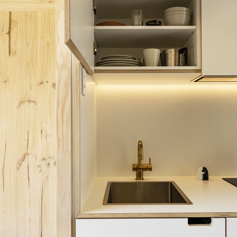 Sink with open storage cupboard above