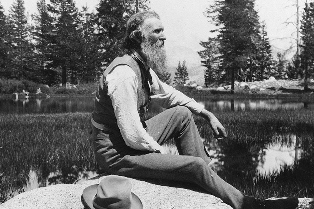 John Muir sitting on rock at lake in 1902