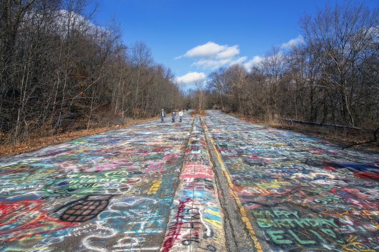 Three people walk down a road covered in graffiti
