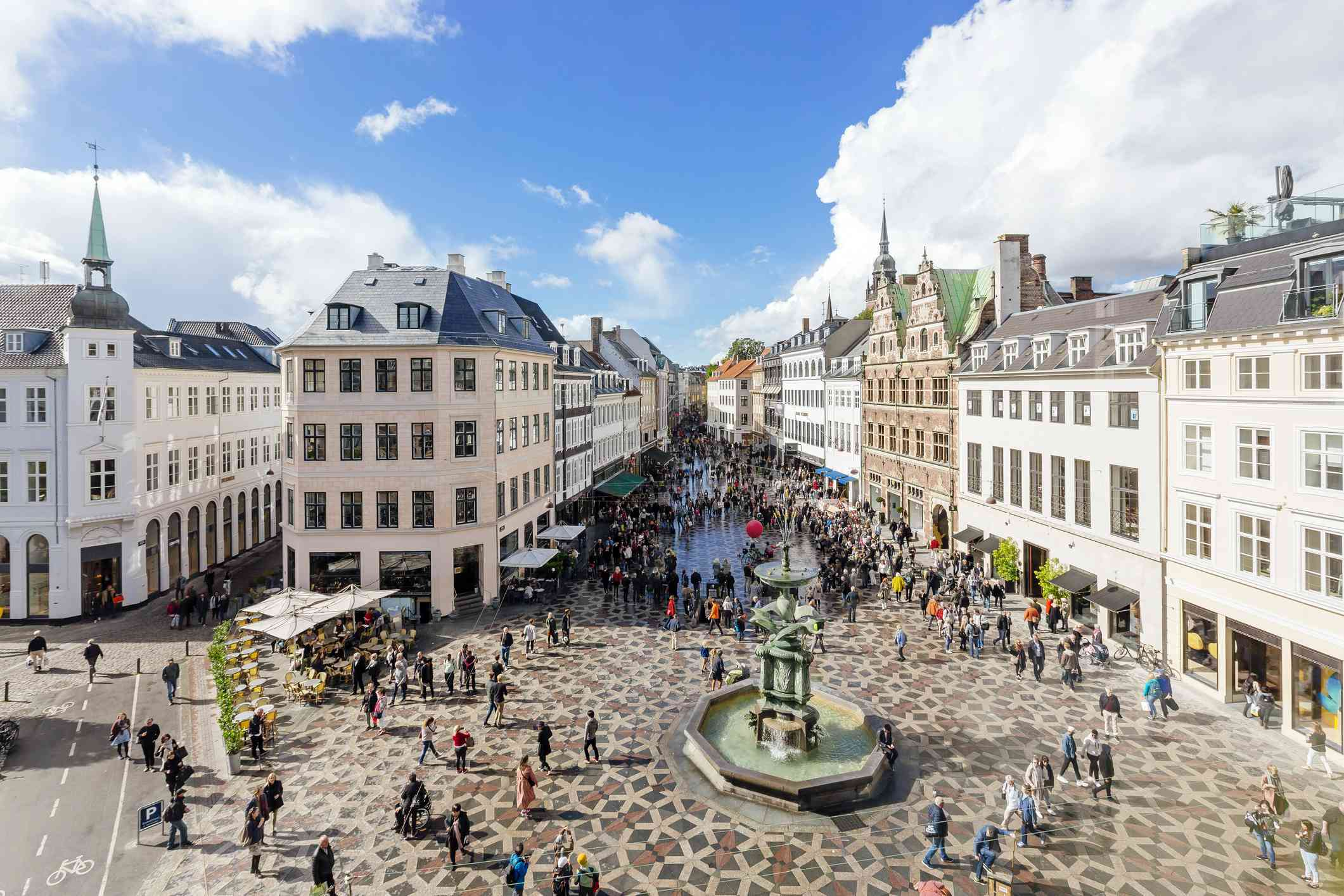 high angle view of people walking around Amagertorv town square with a fountain in the center on buildings on either side in Copenhagen on a sunny day under a blue sky with white clouds