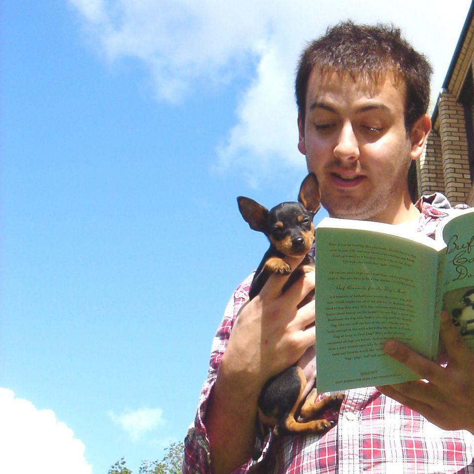 A man with a dog on his shoulder reads a book