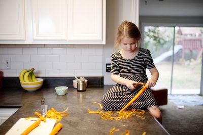 child peels carrots on countertop