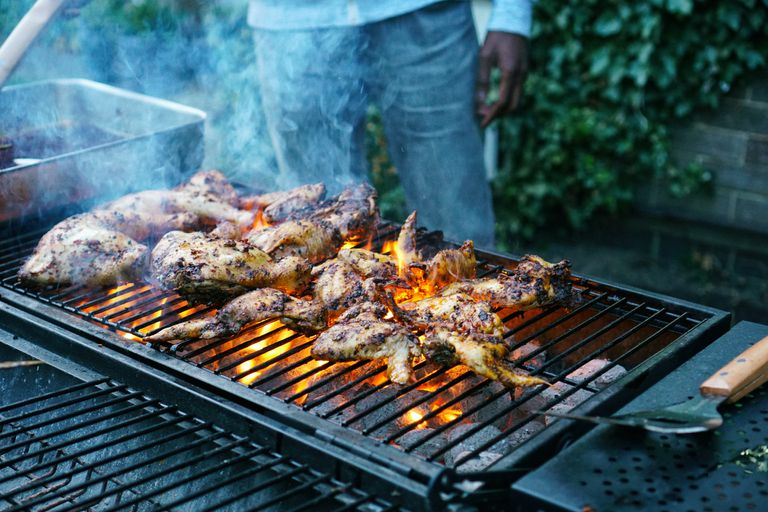 Meat grilling on a grill with man standing behind