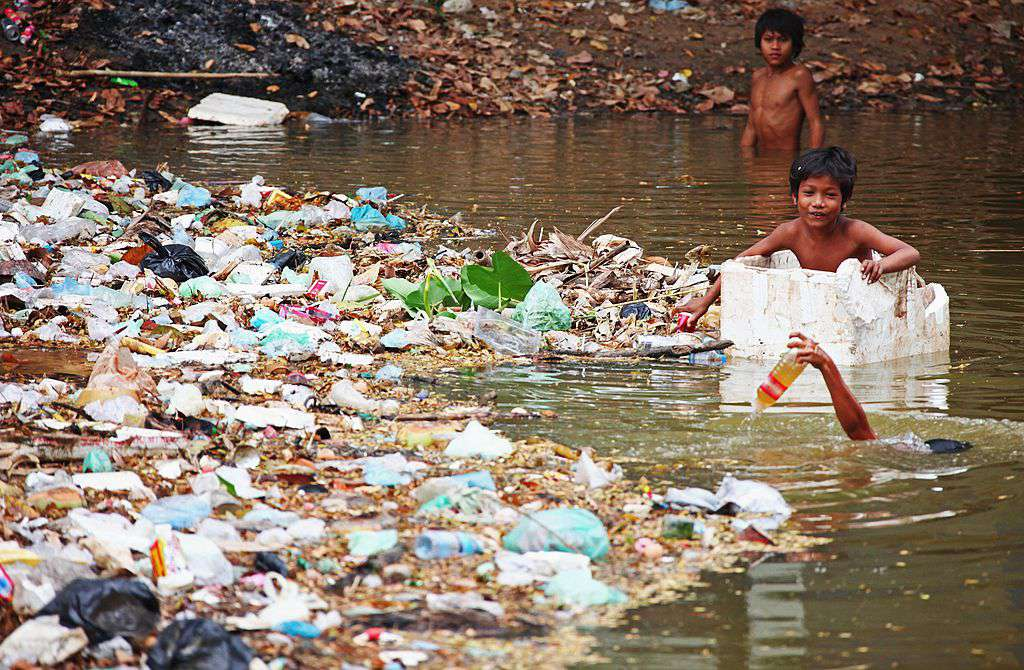 Boys collect bottles among the trash of a river