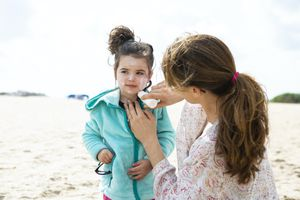 mother applies sunscreen to child