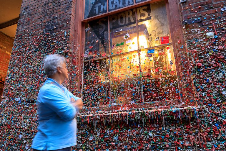 A tourist looking at a wall of gum