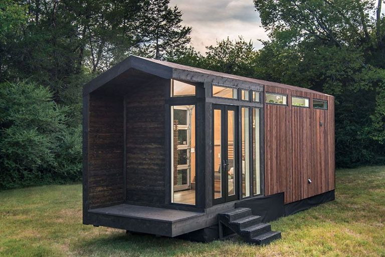 Exterior of a wood-paneled tiny house with trees in the background