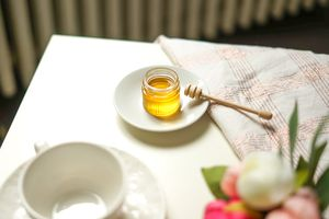 jar of honey with wooden dipper sits on table with flowers
