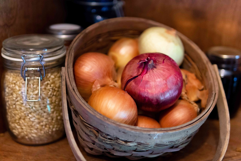 basket of onions in dark pantry