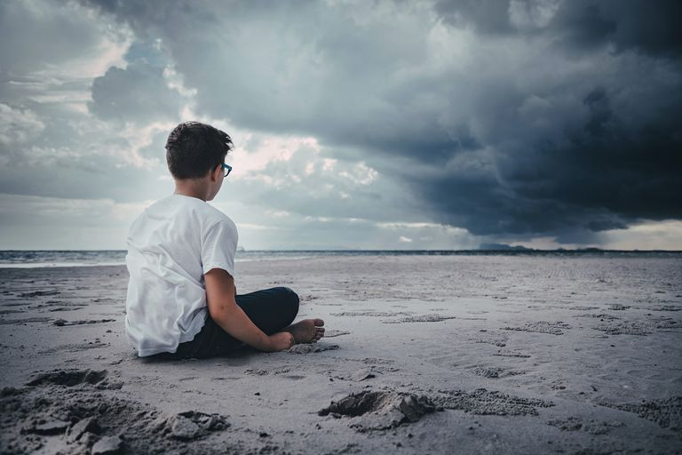 boy sitting alone on stormy beach