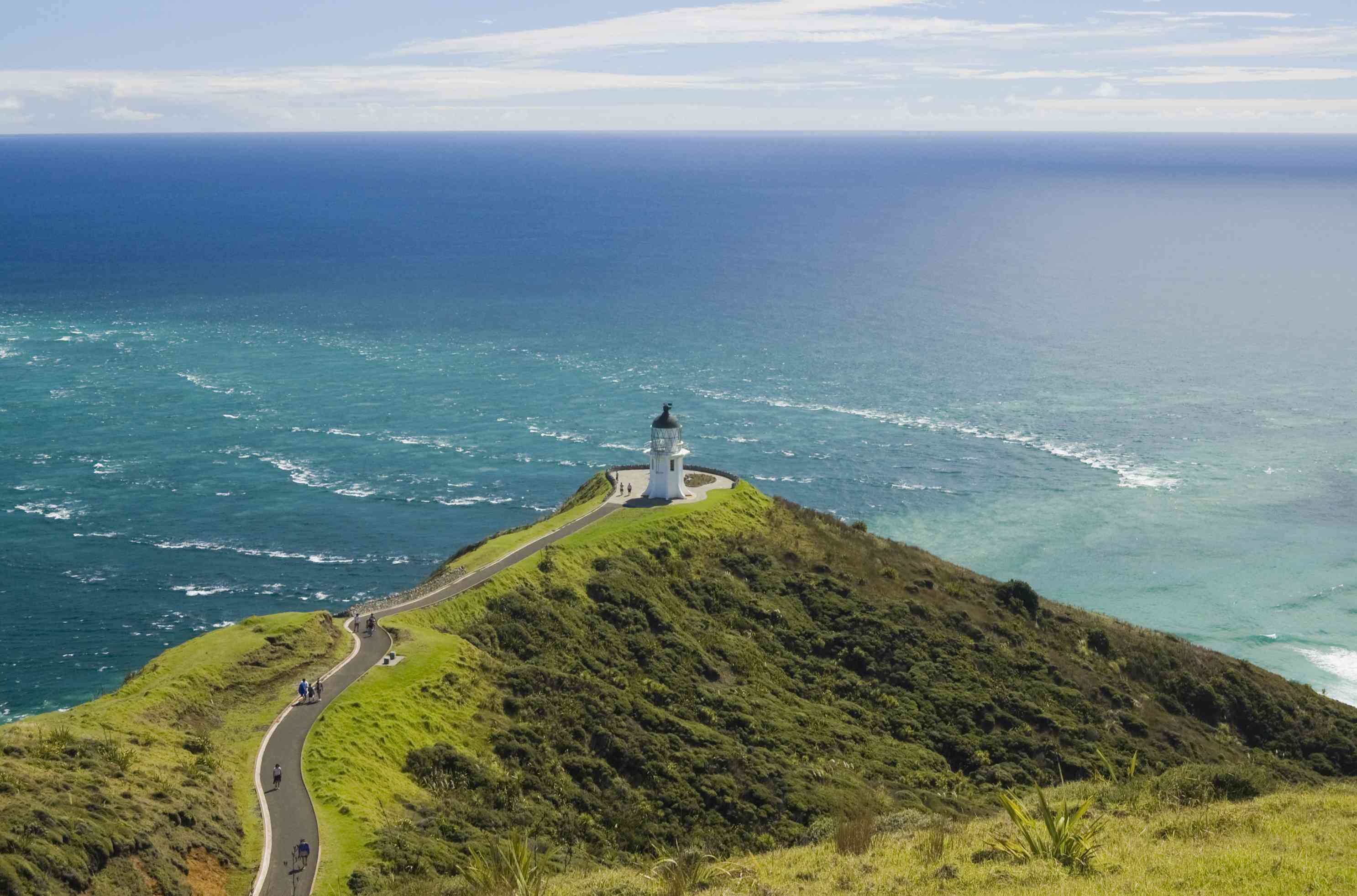 Aerial view of the Cape Reinga lighthouse atop a mountain covered in lush green vegetation where the Tasman Sea and the Pacific Ocean meet