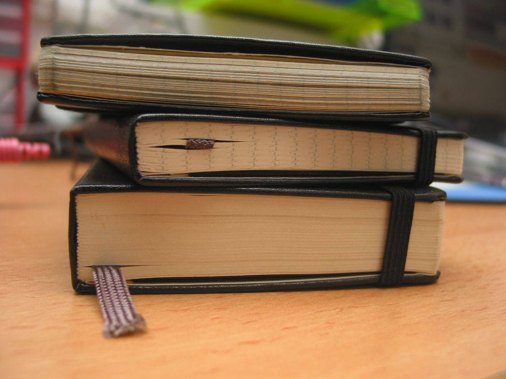 Stack of three moleskine notebooks on a table