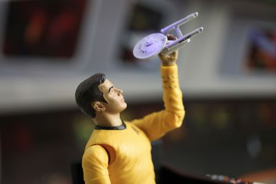 A model of James T. Kirk playing with a replica of the Starship Enterprise.