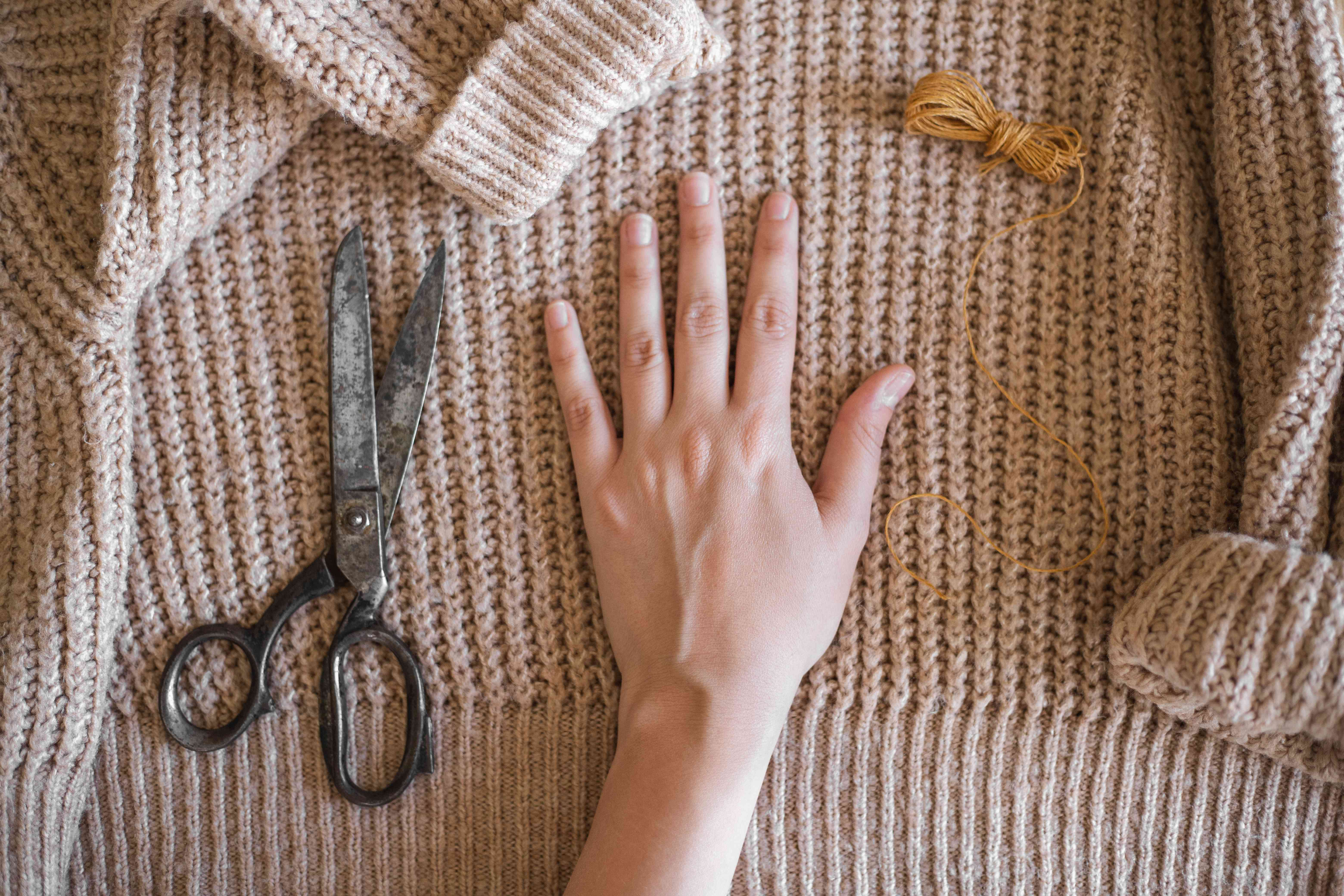 hand lays flat on tan chunky sweater to measure out with scissors and thread