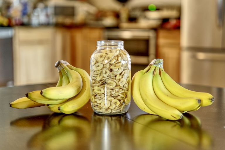 large glass jar of dried banana chips flanked by two bunches of fresh bananas