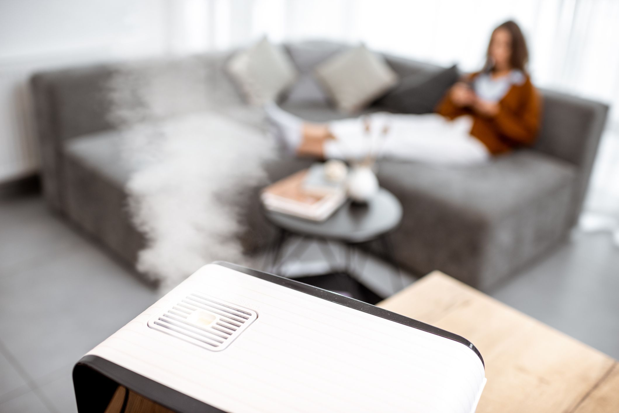 A woman sits on the couch in front of a humidifier.