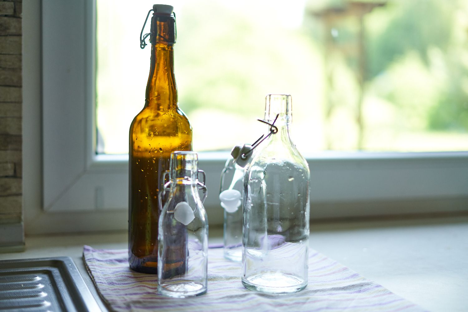 various sized glass flip-top bottles recently cleaned next to kitchen sink