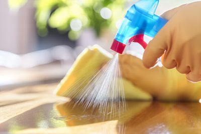 Cleaner being sprayed on a wood surface.