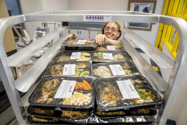 worker with trays of food