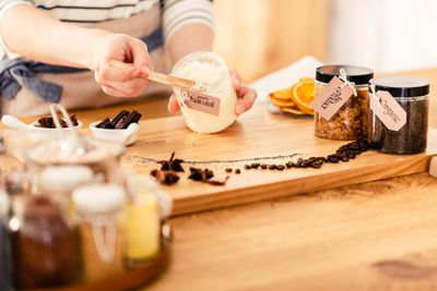 A woman makes homemade body scrubs with organic ingredients on a wood counter.
